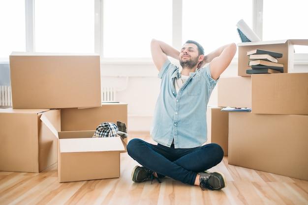 Nadenkende man zit in yoga pose, housewarming