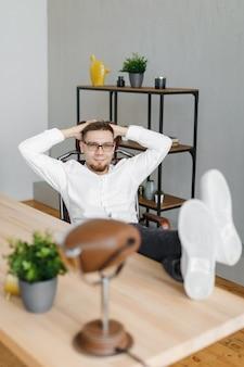 Nadenkende man zit met voeten op tafel in kantoor