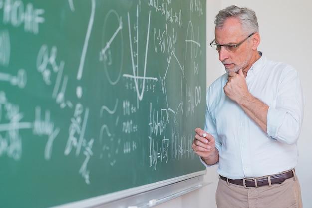 Nadenkende mannelijke leraar die zich op bord bevindt en krijt houdt