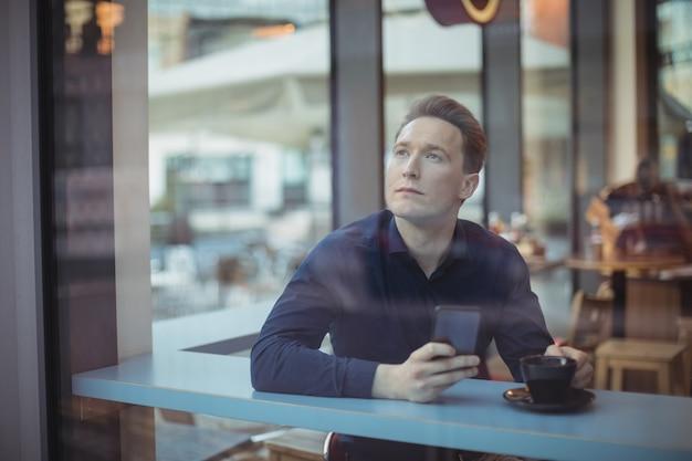 Nadenkende mannelijke uitvoerende die mobiele telefoon houdt
