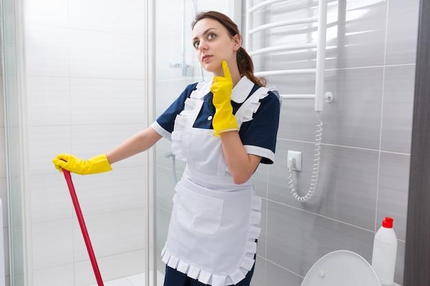 Nadenkende meid staat in de lucht te staren met haar vinger naar haar kin terwijl ze pauzeert bij het schoonmaken van de badkamervloer