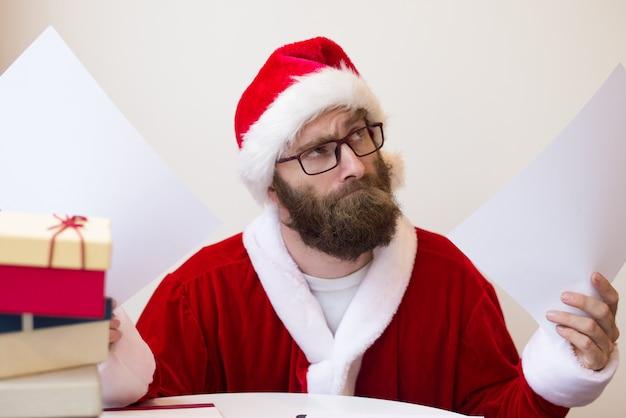 Nadenkende mens die het kostuum van de kerstman draagt en documenten opheft