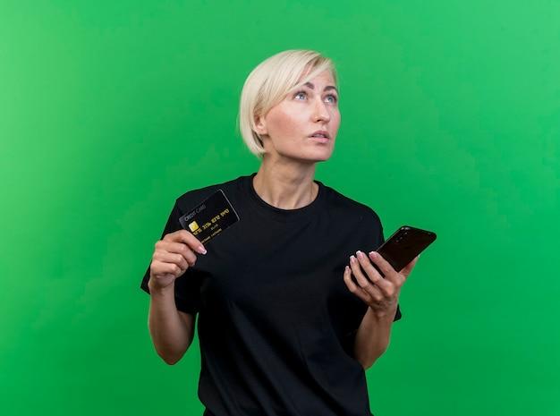 Nadenkende middelbare leeftijd blonde slavische creditcard van de vrouwenholding en mobiele telefoon die omhoog geïsoleerd op groene achtergrond met exemplaarruimte kijken