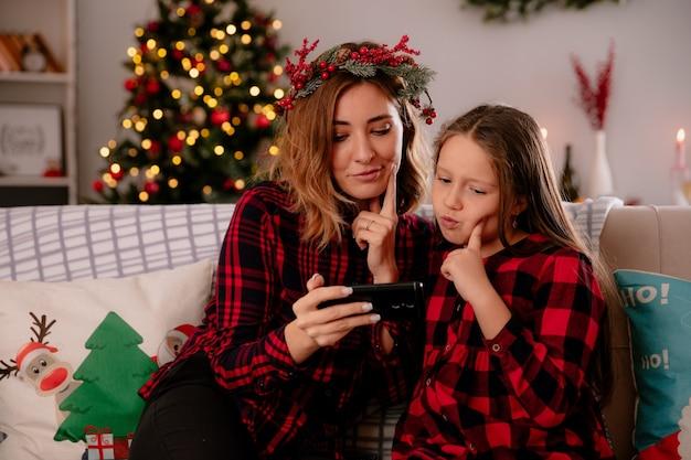 Nadenkende moeder en dochter kijken naar de telefoon terwijl ze op de bank zitten en genieten van de kersttijd thuis at