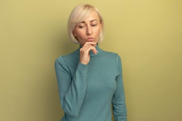 Nadenkende mooie blonde slavische vrouw houdt kin en kijkt neer geïsoleerd op olijfgroene muur