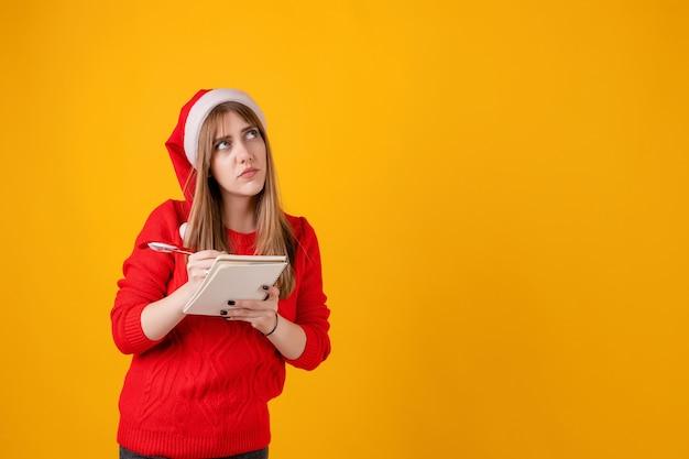 Nadenkende mooie het notitieboekje van de meisjesholding het schrijven nota's en nieuwe jaarplannen met pen die santahoed draagt