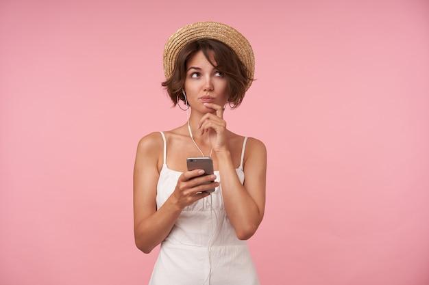 Nadenkende mooie jonge vrouw met casual kapsel die haar kin met opgeheven hand vasthoudt en peinzend opzij kijkt, mobiele telefoon in handen houdt terwijl hij staat