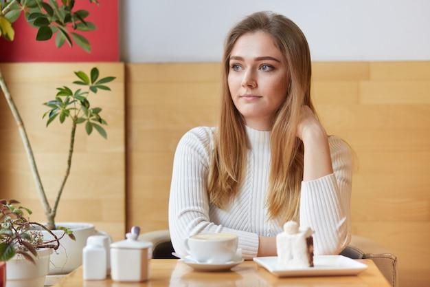 Nadenkende mooie vrouw peinzend opzij, drinkt espresso en eet heerlijke cake in de coffeeshop
