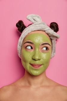 Nadenkende mooie vrouw van gemengd ras geeft om huid en teint, past een voedend groen masker op het gezicht toe, draagt een hoofdband, twee haarbroodjes, staat blote schouders, geconcentreerd opzij. spa-procedures