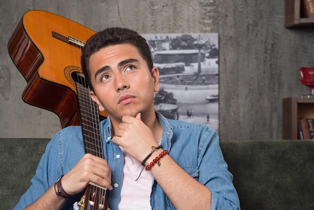 Nadenkende musicus die een mooie gitaar houdt en op bank zit. hoge kwaliteit foto