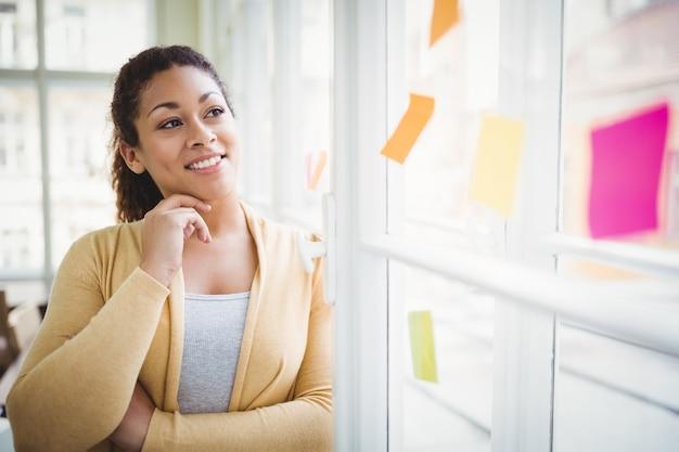 Nadenkende onderneemster die zelfklevende nota's in creatief bureau bekijken