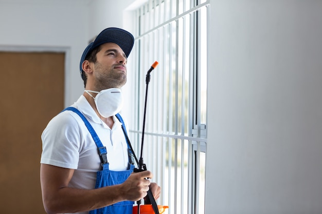 Nadenkende ongediertewerker die met spuitbus omhoog kijkt