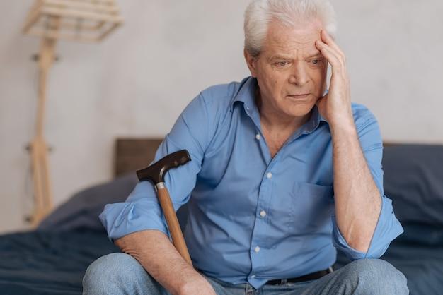 Nadenkende, ongezellige bejaarde man die een wandelstok vasthoudt en zijn hoofd vasthoudt terwijl hij bij zijn gedachten betrokken is