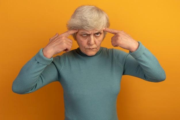 Nadenkende oude vrouw die een blauwe coltrui draagt en een denkgebaar doet