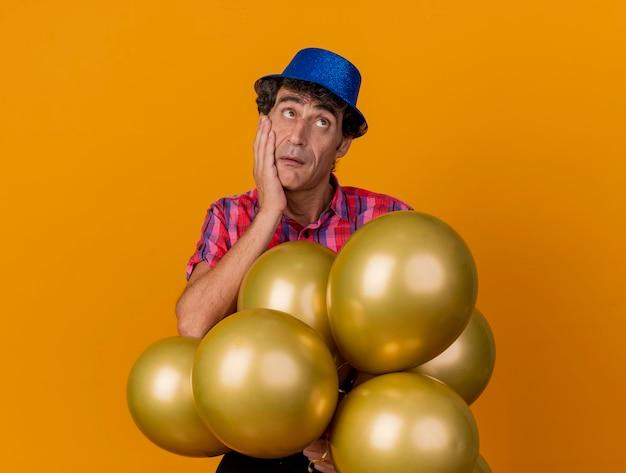 Nadenkende partijman van middelbare leeftijd die partijhoed draagt die ballons houdt die hand op gezicht houdt die omhoog kijkt geïsoleerd op oranje muur met exemplaarruimte
