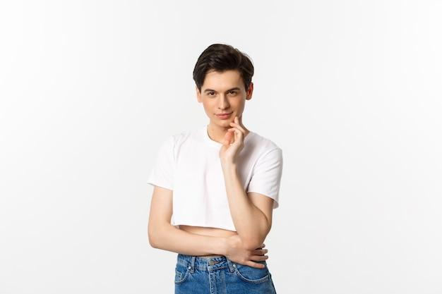 Nadenkende queer jongeman met crop top, glimlachend en camera sluw kijken, met een idee, staande op witte achtergrond.