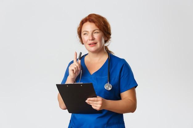 Nadenkende roodharige vrouwelijke arts, roodharige arts in blauwe scrubs die geïntrigeerd kijken door patiëntengeval, pen schudden en klembord vasthouden.