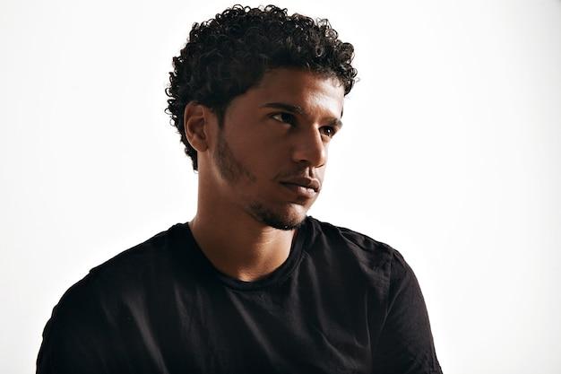 Nadenkende rustige jongeman met een leeg zwart katoenen t-shirt op een witte muur