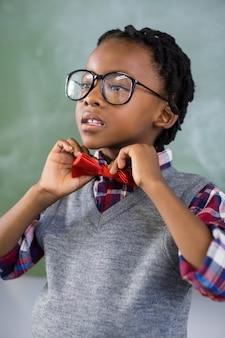 Nadenkende schooljongen die een vlinderdas in klaslokaal aanpassen