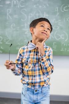 Nadenkende schooljongen die zich met hand op kin in klaslokaal bevinden