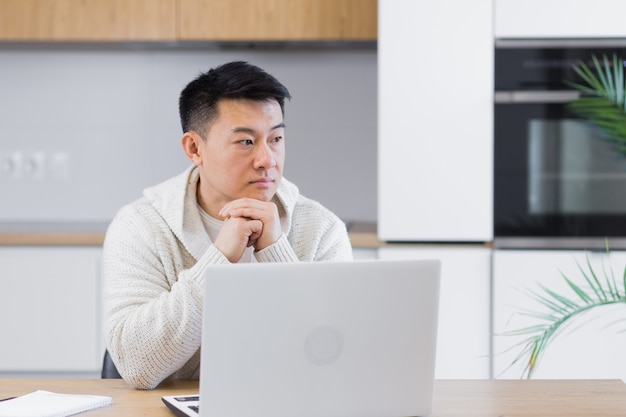 Nadenkende serieuze jonge aziatische man die wegkijkt student schrijver zit thuis bureau met laptop