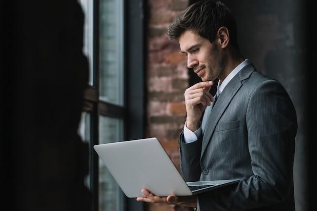 Nadenkende slimme jonge zakenman die laptop bekijkt