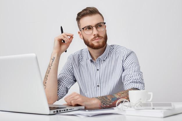 Nadenkende slimme mannelijke student met trendy haido kijkt bedachtzaam opzij terwijl hij gedachten probeert te verzamelen, op cursuspapier werkt, voor geopende laptop zit,
