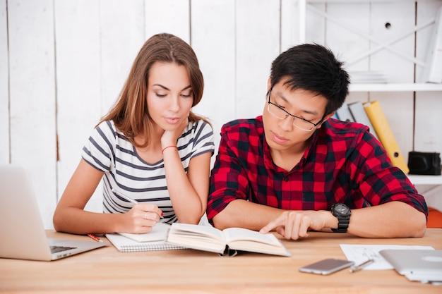 Nadenkende studenten die in de klas zitten terwijl ze naar een boek kijken en educatief materiaal leren