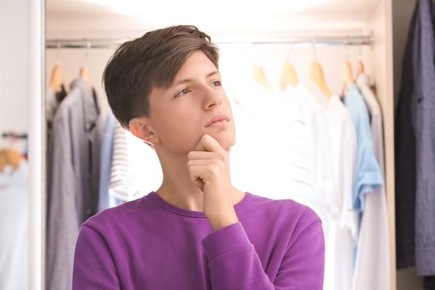 Nadenkende tiener dichtbij kleerkast thuis