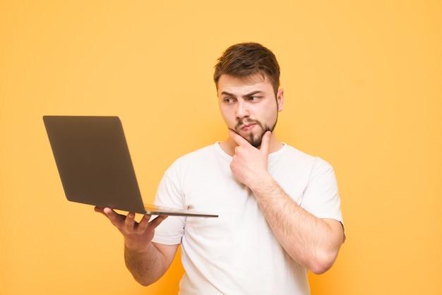 Nadenkende tiener met een baard gekleed in een wit t-shirt staat op geel
