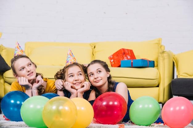 Nadenkende tienermeisjes leng op het tapijt met kleurrijke ballonnen in de woonkamer