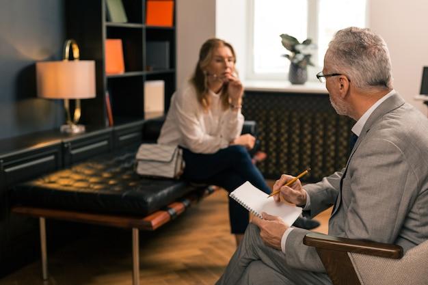 Nadenkende trieste vrouw zittend op de bank in haar kantoor psychoanalytici terwijl denken en wegkijken