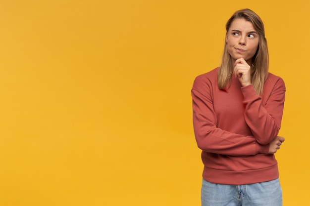 Nadenkende twijfelende blonde vrouw. samengetrokken lippen. kijkend naar de linkerbovenhoek staand met de hand gevouwen aan de rechterkant geïsoleerd