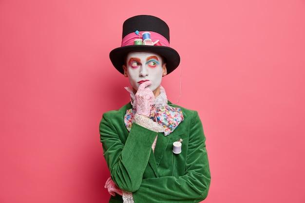 Nadenkende vakantieganger denkt na over hoe hij mensen op feest gekleed in hoedenmaker-kostuum kan vermaken, draagt kleurrijke make-up poses peinzend tegen roze muur