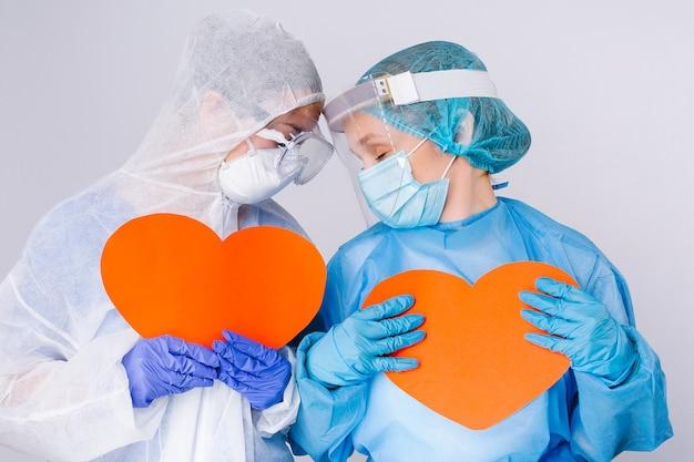 Nadenkende, vermoeide doktoren in uniform met grote rode harten in hun handen. valentijnsdag, liefdadigheid, teruggeven, pandemie