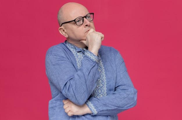 Nadenkende volwassen man in blauw shirt met een bril die zijn kin vasthoudt en naar de zijkant kijkt