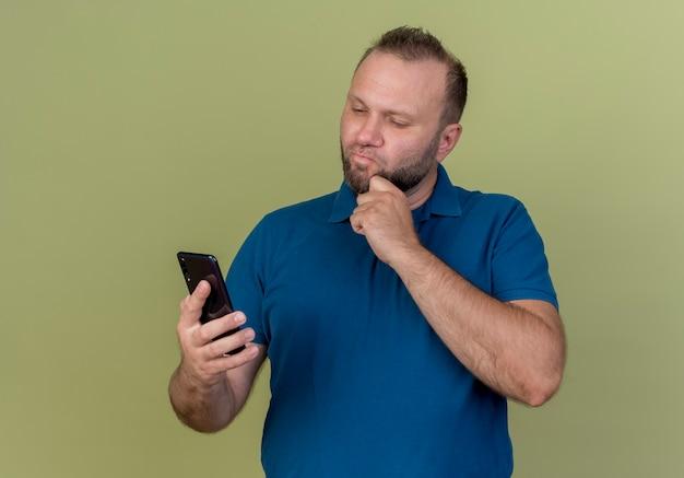 Nadenkende volwassen slavische man houden en kijken naar mobiele telefoon en kin aan te raken