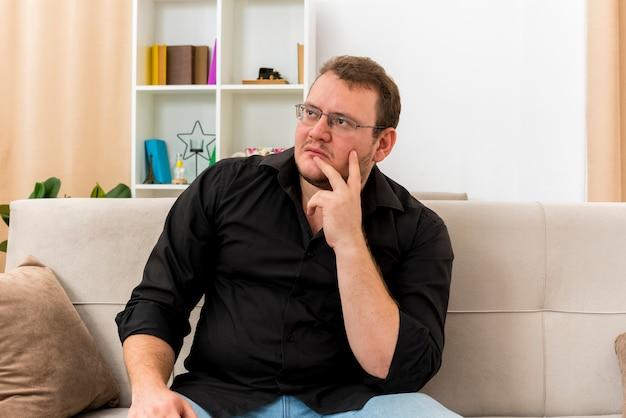 Nadenkende volwassen slavische man in optische bril zit op fauteuil hand op kin in de woonkamer te zetten