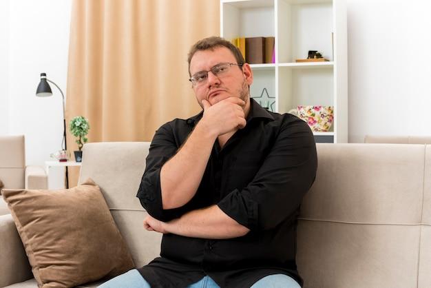 Nadenkende volwassen slavische man in optische bril zit op fauteuil kin vast te houden en kant in de woonkamer te kijken