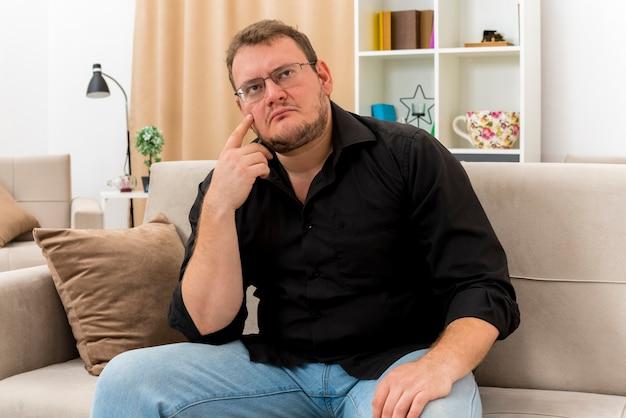 Nadenkende volwassen slavische man in optische bril zit op fauteuil zetten vinger op gezicht kijken kant in de woonkamer