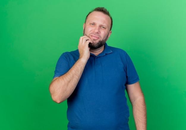 Nadenkende volwassen slavische man kin geïsoleerd op groene muur met kopie ruimte aan te raken