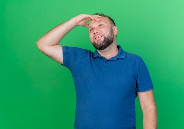 Nadenkende volwassen slavische mens die hand op hoofd zet die omhoog geïsoleerd op groene muur kijken