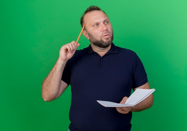Nadenkende volwassen slavische mens die het potlood en het blocnote van de zijholding bekijken wat betreft hoofd met potlood dat op groene muur wordt geïsoleerd