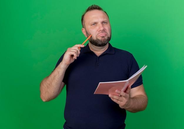 Nadenkende volwassen slavische mens die recht met potlood en notitieblok kijkt wat betreft wang met geïsoleerd potlood