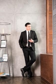 Nadenkende volwassen zakenman die met smartphone weg kijken