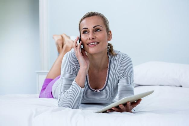 Nadenkende vrouw die digitale tablet houden terwijl het spreken op telefoon op bed