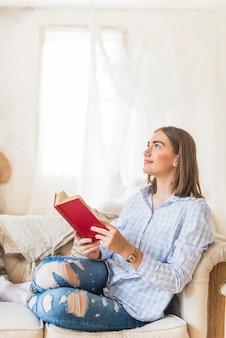 Nadenkende vrouw die een boek op bank leest