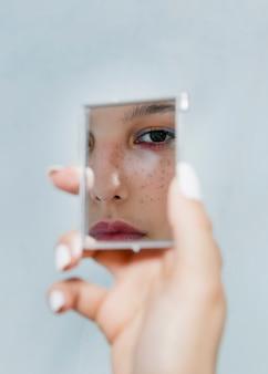 Nadenkende vrouw die in een spiegel kijkt