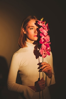 Nadenkende vrouw die roze bloem houdt