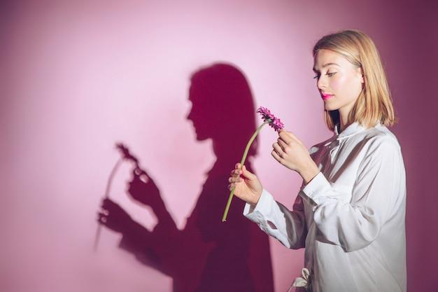 Nadenkende vrouw die roze gerberabloem bekijkt